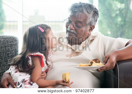 Portrait of Indian family at home. Grandparent and grandchild eating butter cake. Asian people living lifestyle. Grandfather and granddaughter.