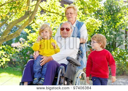 Two Little Kid Boys, Their Grandmother And Grandfather In Wheelchair