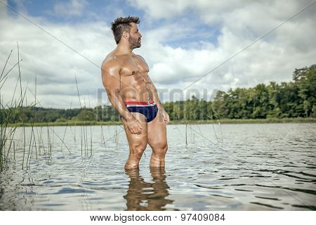 An image of a muscular man in the lake with a white shirt and sunglasses