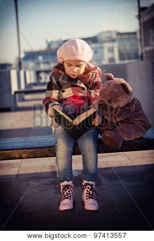 Girl Sits On A Bench And Reads The Book To A Toy Bear