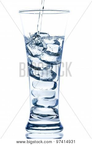 Pouring Water In An Elegant Tall Glass With Ice And Water Drops On White Background