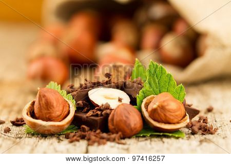 Hazelnut With Chocolate Bars And Green Leaves On Old Wooden Background