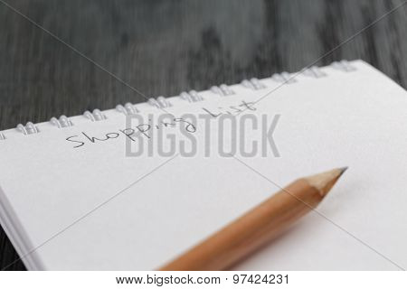 closeup photo of open empty notepad with shopping list phrase