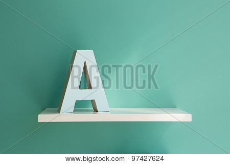 Letter A on a white shelf.