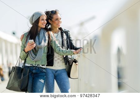 Two Young Women Looking Over A Dock Fence