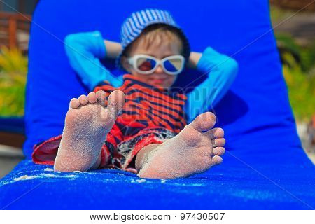 feet of child relaxed and enjoying summer beach