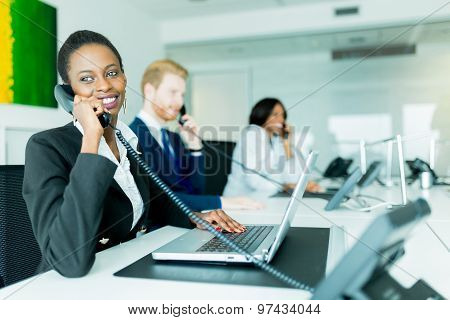 A Beautiful, Black, Young Woman Working At A Call Center In An Office With Her Red Haird Partner On