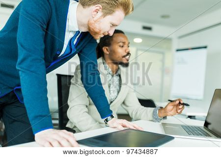 Two Colleagues Discussing Graphics Design Flaws In A Nice White Office