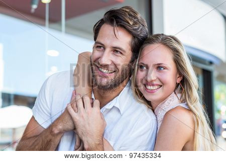 Smiling woman putting arm around her boyfriend at shopping mall
