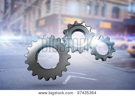 Metal cogs and wheels connecting against blurred new york street