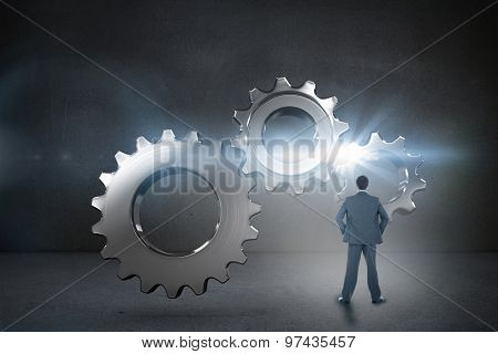 Businessman standing with hands on hips against black wall