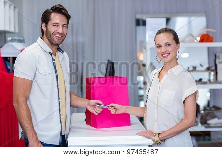 Portrait of smiling woman giving credit card to cashier in clothing store