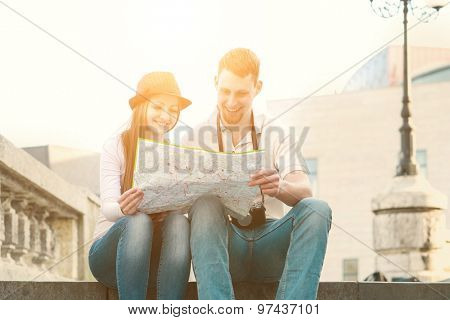 Touristic couple looking at map on the city street