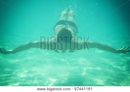 Woman swimming underwater in the turquoise sea water