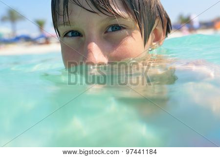 little boy swimming in sea with clean turquoise water transparent
