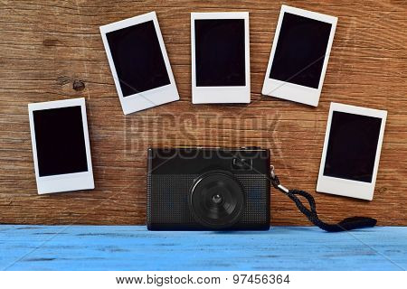 a retro camera and some blank instant photos attached to a rustic wooden surface