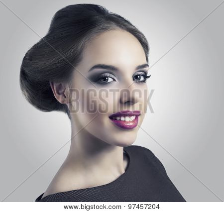 beautiful model with retro makeup and hair style against light grey studio background, isolated