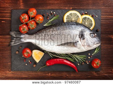 Fresh Fish, Lemon, Spices And Tomatoes On A Board