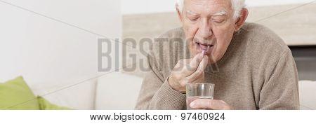 Senior Man Taking Tablet