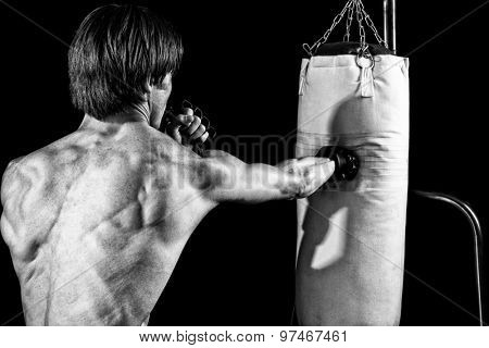 Young adult martial artist with heavy bag. Studio shot over black. Black and white.