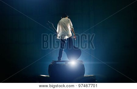 Guitarist on stage playing with great electric guitar under blue light