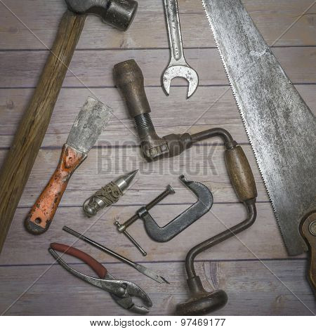 Old rustic tools with aged patina and aged charm - moody lighting capturing the atmosphere of a shed or work room.