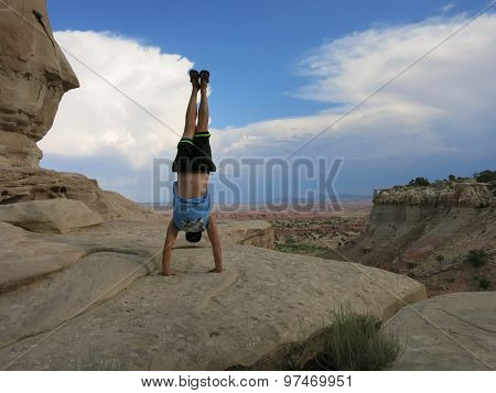 Man Does Handstand On Cliffs With Field Landscape In The Desert Mountain