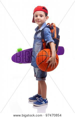Portrait of a school boy holding a skateboard and a basketball on white background