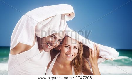 Joyful couple on the beach, happy enamored woman and man peeking from the towel, having fun on tropical resort, with pleasure spending honeymoon