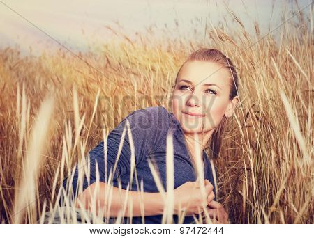 Beautiful woman lying down on golden wheat field in sunset light, relaxation in countryside, enjoying beauty of autumn nature