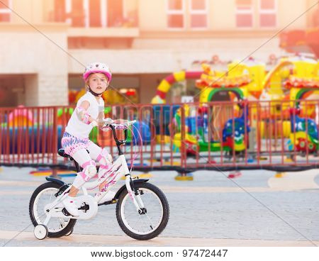 Cheerful little girl riding on the bicycle in amusement park, happy carefree childhood, having fun outdoors in summer camp