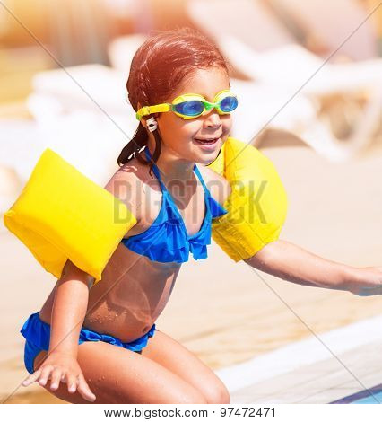 Little girl on the beach, having fun near swimming pool and preparing to jump into the water, spending summer holidays on beach resort