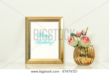 Picture mock up with golden frame amd flowers. Vintage style interior. Sample text Happy Birthday! Retro toned photo