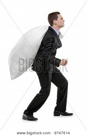 Full Length Portrait Of A Businessman Carrying A Money Bag