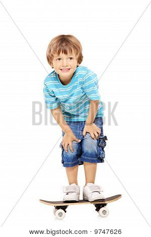 Full Length Portrait Of An Adorable Young Boy Riding A Skateboard