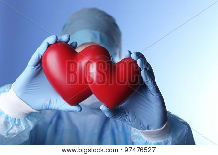 Doctor holding decorative hearts on blue background