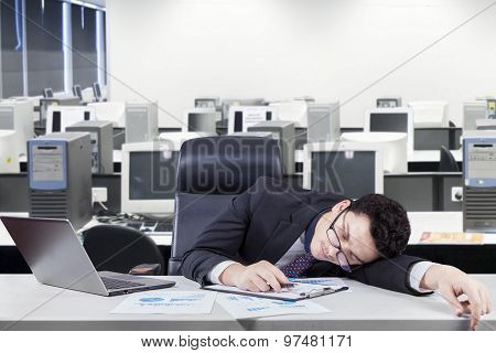 Tired Worker Napping At Workplace