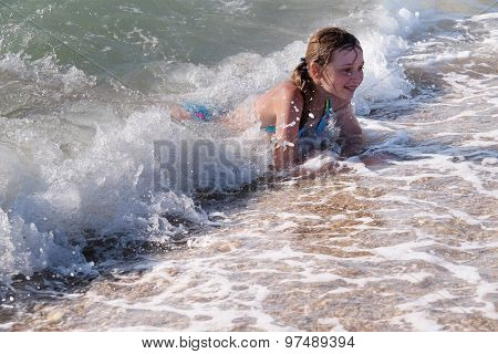 Children play in a sea surf