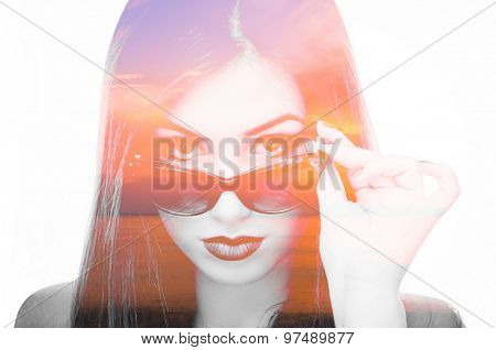 Double exposure photo of a beautiful young woman with sunglasses and sunset over the sea