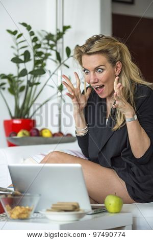Young business woman looking at a laptop in a state of shock. Stress, fear, shock.