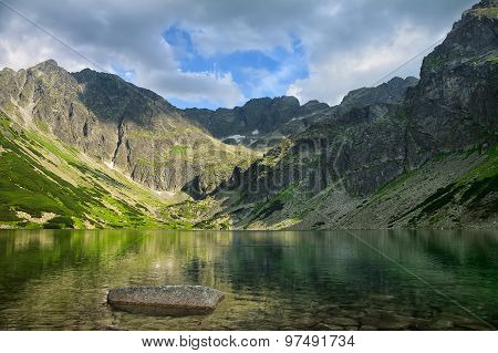 Clear Crystal Lake With Transparent Water Surrounded By Beautiful Mountain Chain