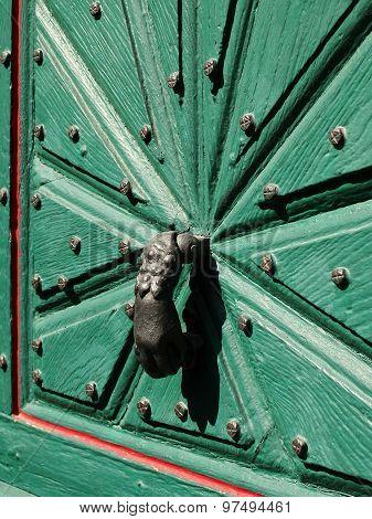 Cast iron door knocker on green rustic timber door