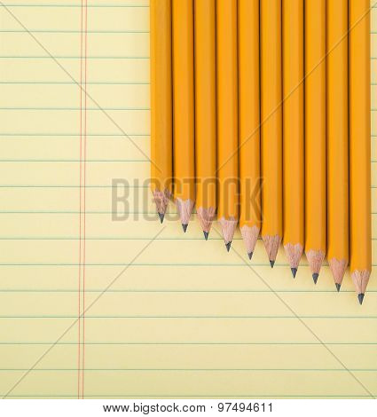 Row Of Yellow Pencils Against A Notepad