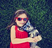 snapshot of a cute girl with sunglasses holding a chihuahua with goggles on in a grassy park or yard poster