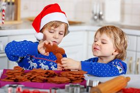 foto of gingerbread man  - Two little kid boys in red santa hat with fresh baked gingerbread cookies - JPG