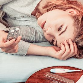 stock photo of laying-in-bed  - Sick woman laying in bed taking tablets pills - JPG