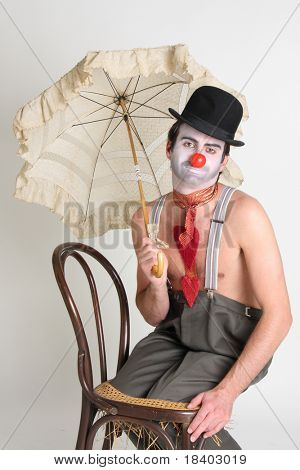 sad clown sitting on a chair