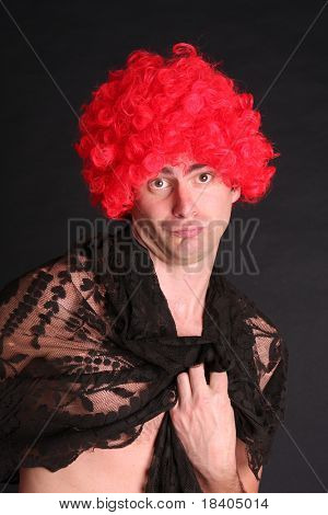 funny young man with a red periwig on his head