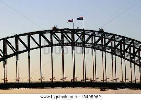 A group of people at the top of the Sydney Harbour Bridge at sunset