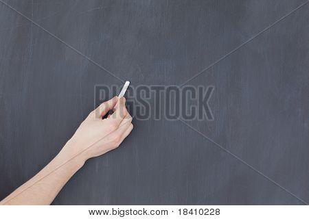 Mano sosteniendo una tiza y y con ganas de escribir en una pizarra